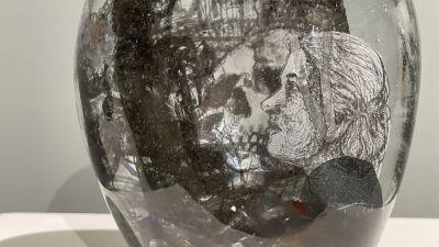 Lähikuva teoksesta, jossa näkyy samaan aikaan naisen sivuprofiili ja veistoksen keskellä pääkallo