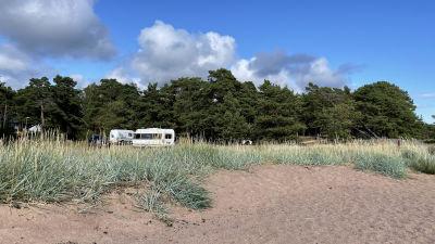 Bild av husbilar som är parkerade på en sandstrand.