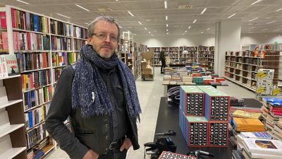 En man framför bokhyllor.
