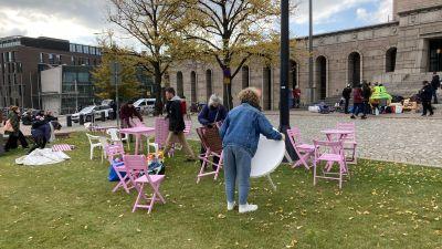 Personer ställer fram bord och stolar på en gräsplätt framför riksdagshuset.