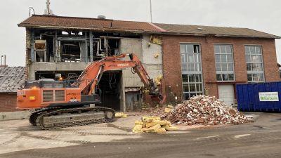 Rivning av byggnad med orange grävmaskin.