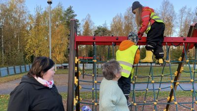 Förskolebarn klättrar i klätterställning medan två pedagoger tittar på.