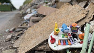 En plastleksak sticker fram i en väldig hög av obestämbart bråte.