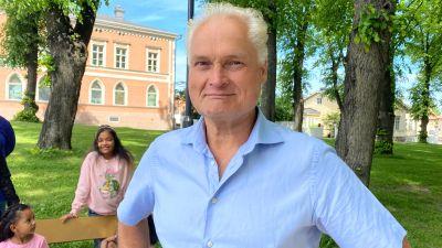En glad äldre man står i en park och tittar leende in i kameran. Bakom honom syns en leende ung flicka samt en yngre lite fundersam flicka.