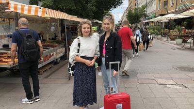 Noora Sutelainen och Wilma Kyllönen står på universitetsgatan i Åbo bredvid ett torgstånd.