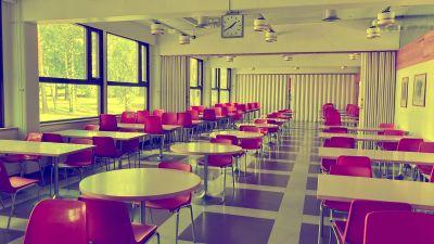 En tom sal med röda stolar och runda bord.