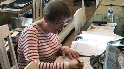 Beatrice Wallman sitter vid ett bord och skriver.