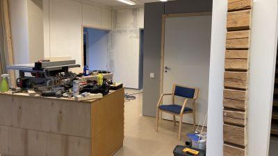 Ett rum där renovering pågår. En arbetsbänk med en mängd verktyg och bråte på.