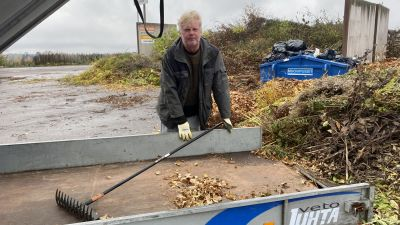 En man står vid en släpvagn intill en lövhög. Han har ena handen på en kratta som ligger på släpkärrsflaket.