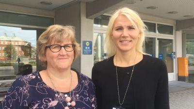 Två kvinnor står utanför sjukhusentré.