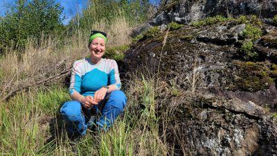 En kvinna med blå-vita utekläder och grönt hårband sitter på en klippa som kantas av gräs och hö.