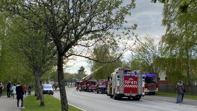 Många har samlats för att se en brand på Hökgatan i Orrnäs i Vasa. Många brandbilar står på rad, på gångvägen står många människor och tittar på. Vår.