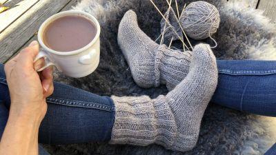Fötter iklädda stickade sockor, stickning och garnnystan på fårfäll. En hand som håller en kopp varm choklad.
