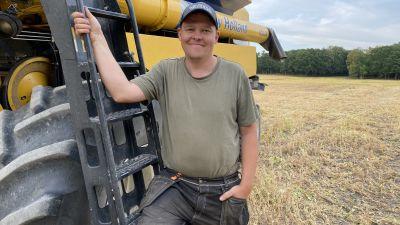 En jordbrukare står vid sin skördetröska på en åker.