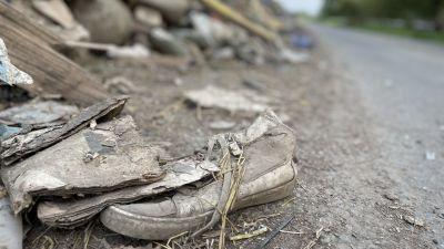 En sko sticker fram ur en hög med obestämbart bråte.