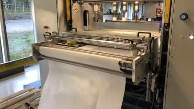 En maskin som veckar filtertyg. Man ser det ovecakde tyget på väg in i mangelliknande maskin.