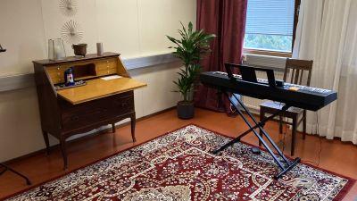 Ett rum med en stor orientalisk matta på golvet, inrett med en sekretär och ett elpiano.