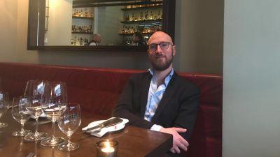 jonathan sitter vid ett dukat restaurangbord. Han bär en mörkgrå kavaj och en vit skjorta.