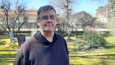 En bild på en man i glasögon, han står i en trädgård