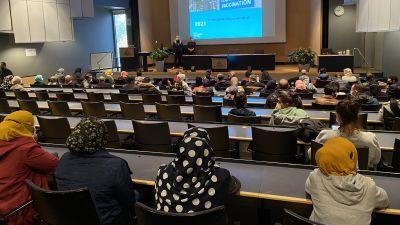 En stor föreläsningssal dä man ger information om coronavaccin. En del av deltagarna har färggranna huvuddukar.