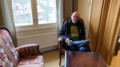 En man sitter i en fåtölj med en kaffekopp i handen.