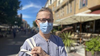 Juhani Jutila, en man i medelåldern med ljusblå tröja och blått munskydd.