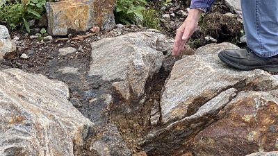En hand visar på en spricka i berget.