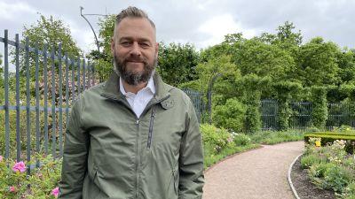 Olof Lundh ser in i kameran med ett blomhav bakom sig.