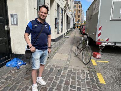 Janne Mäkelä står på en gata i Köpenhamn med en finsk landsladströja.