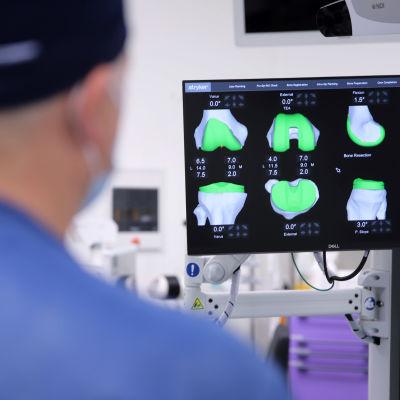 Ortopedi tutkii näytöltä 3D-kuvia leikkaussalissa.