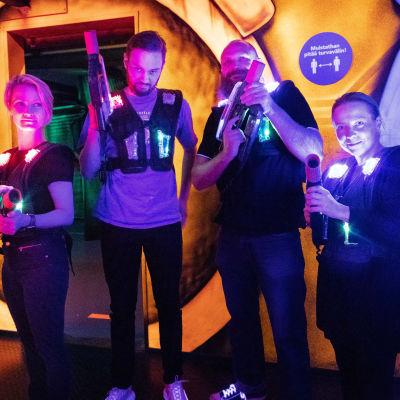 Megazone pelaajia värivaloliivit päällä ja aseet käsissään poseeraavat kameralle