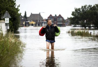 En man tar sig igenom en översvämmad gata i Arcen, Nederländerna.