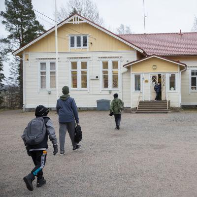 Ala-astelaiset juoksevat sisälle Hajalan kouluun.