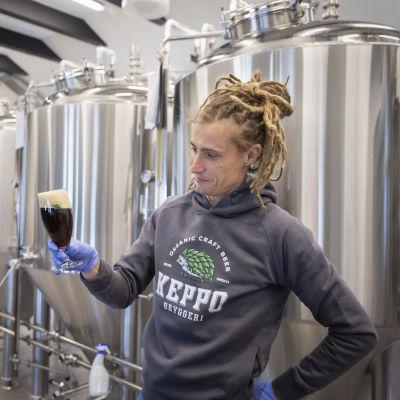 Mies katselee täyteen kaadettua olutlasia. Taustalla on isoja oluen panemiseen käytettäviä metallisia tankkeja.