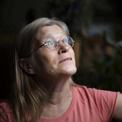 Liisa Kuusipalo katsoo ikkunasta ulos kotonaan Polvijärvellä