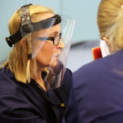 Hoitotyön lehtori Pirjo Heimo käyttää suojavisiiriä opettaessaan sairaanhoitajaopiskelijoita.