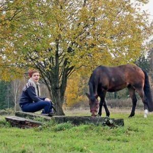 Hevonen syö ruohoa ja nainen istuu