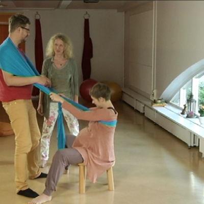 Fysioterapeutti Malla Rautaparta näyttää Puoli seiskan Paavo Häikiölle, miten isä voi tukea jakkaralla synnyttävää äitiä esimerkiksi kantoliinan avulla.