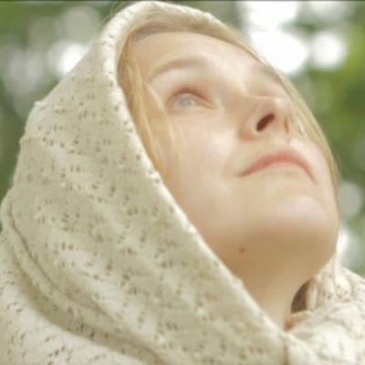 Kuvassa nainen katsoo taivaalle.