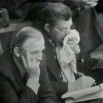 Mustavalkoinen kuva, jossa kaksi miestä istuvat tylsistyneinä