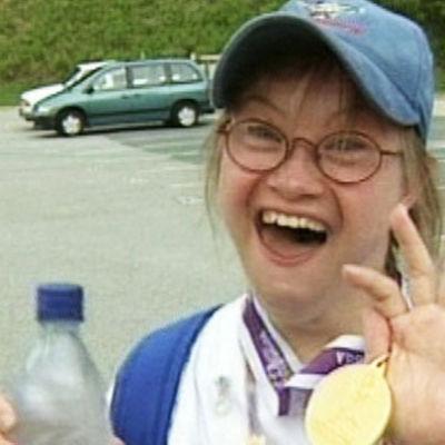 Suomen Special Olympics -joukkueen urheilija näyttää riemuiten mitaliaan.