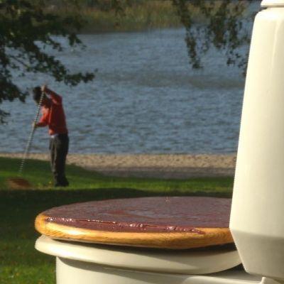 Wc-stol på gräsmattan med nytt lock och med Jim Björni räfsande i bakgrunden.