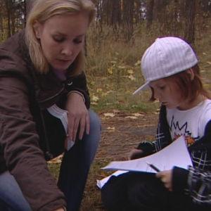 Tyttö metsässä opettajan kanssa