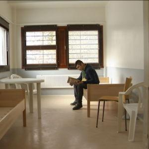 Ferhat försöker läsa en bok på finska i ett familjerum. Vi besökte inte hans eget rum, som han delar med en annan asylsökande.
