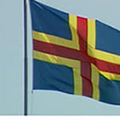 Ahvenanmaalaisia ja itsehallinnon symboleita: lippu ja postimerkki vuodelta 1990