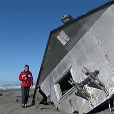 Toimittaja Mika Mäkeläinen sortuneen talon edustalla Alaskassa