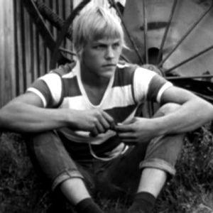 Nuori mies istuu ruohikolla