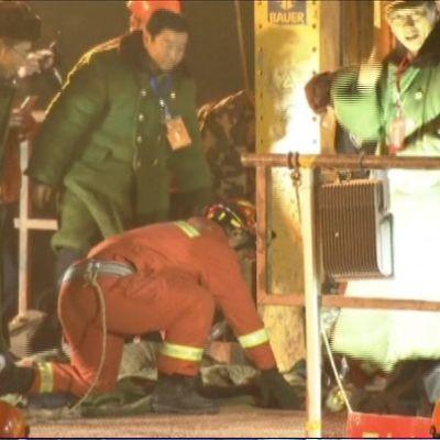 Miehiä kurkistelee aukkoon, josta kaivosmiestä nostetaan.