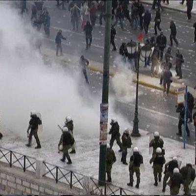 Mellakkapoliiseja ja mielenosoittajia kadulla savupilven erottamina.