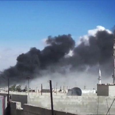 Mustaa savua nousee sinistä taivasta vasten.